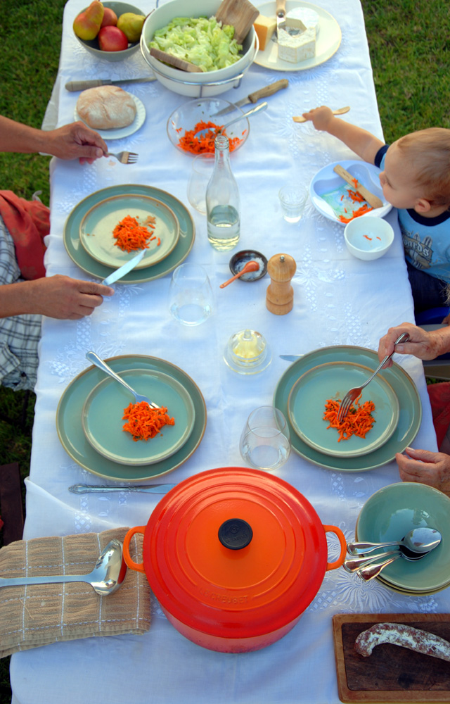 A French family, including a baby, is at a table having a four course meal