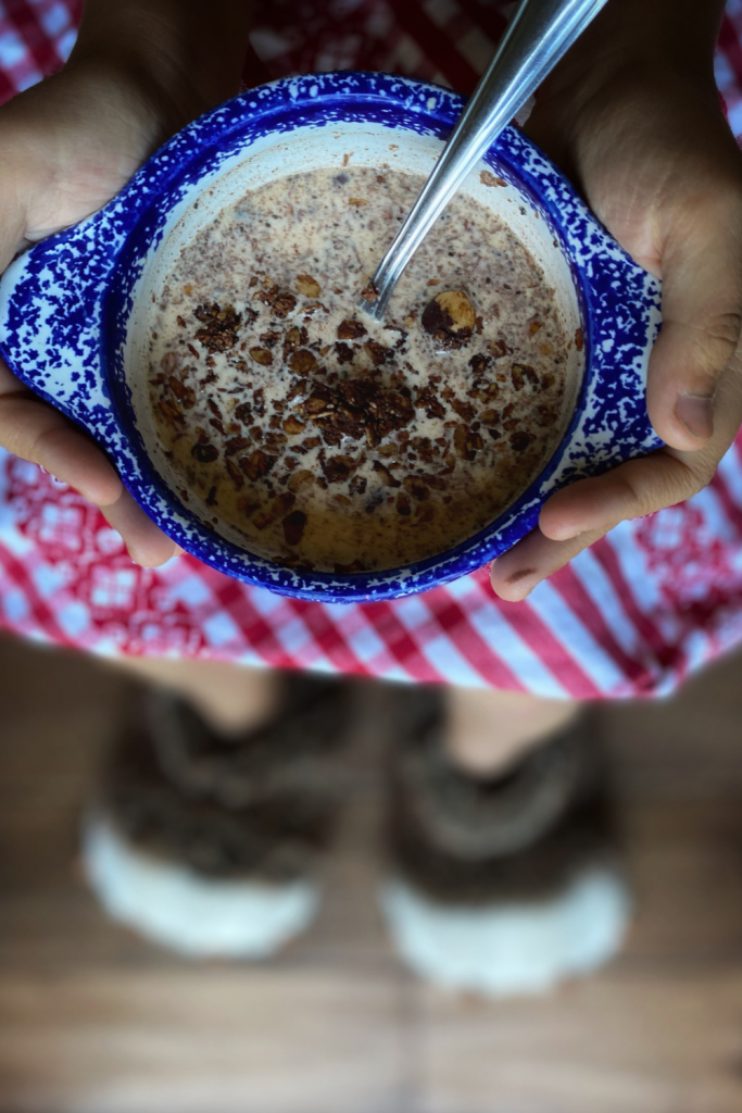 a child holding a bowl of homemade chocolate hazelnut granola in milk