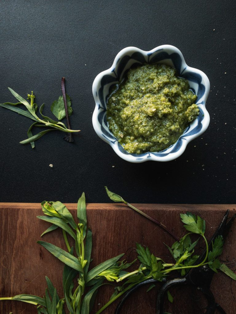 a bowl of pesto with herbs