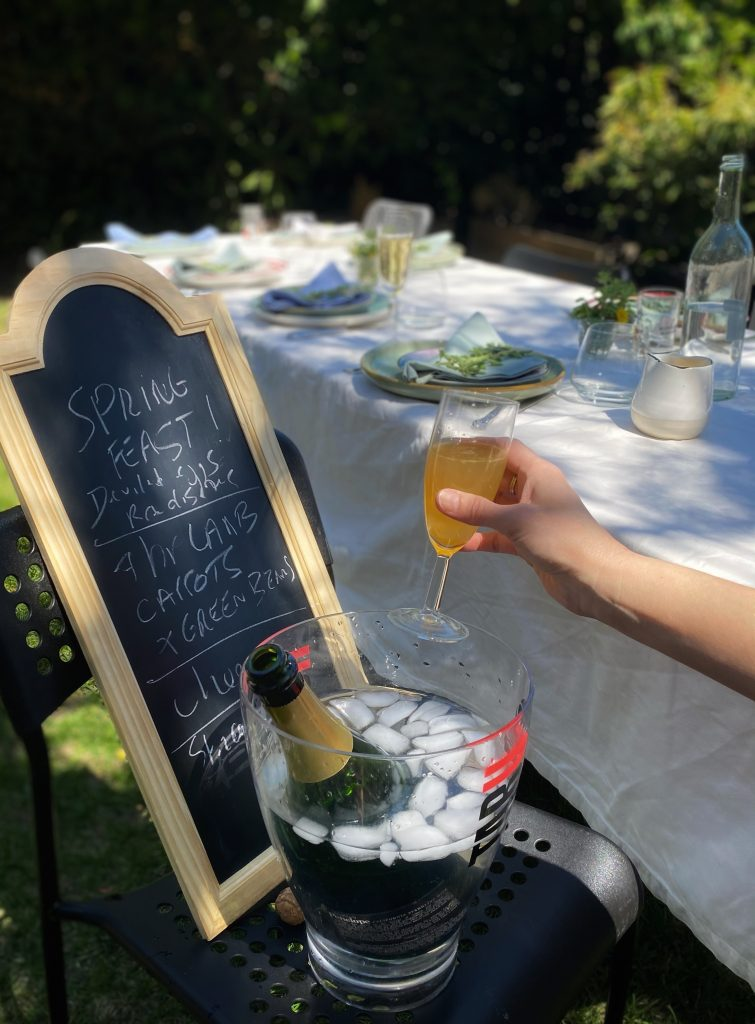 A festive Easter dinner table set outside, and a hand holding a glass of champagne in front of a spring feast menu board